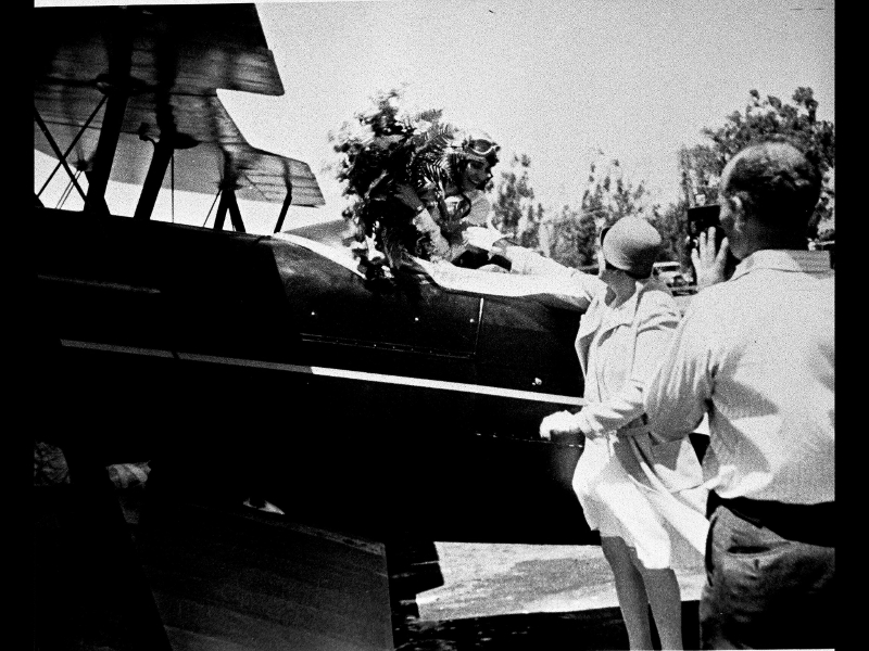 Woman pilot with flowers being photographed in her cockpit at the Powder Puff Derby, the first all-women's transcontinental Air Derby from Santa Monica to Cleveland, 1929