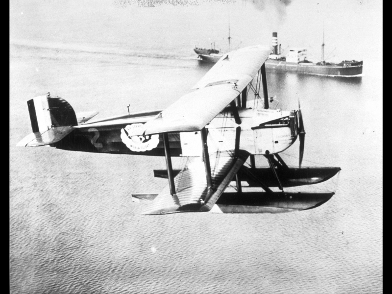 A Douglas World Cruiser on world flight with a ship traveling the ocean below the airplane, 1924