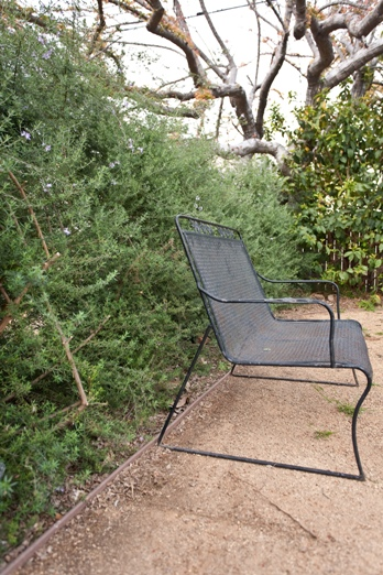 This seating area is nestled in the back yard surrounded by a low hedge of rosemary with a ground cover of permeable decomposed granite.